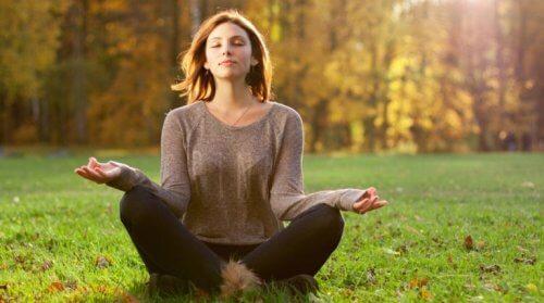 Frau, die im Wald meditiert