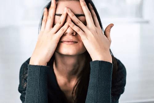 Frau legt sich die Hände vors Gesicht