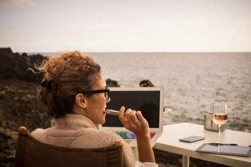 Nomadin mit Rechner und Wein am Meer