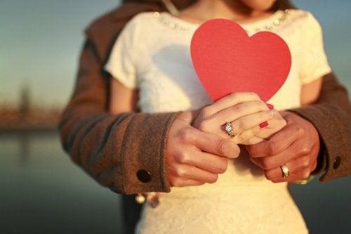 Ein Paar hält gemeinsam ein Herz aus Pappkarton.