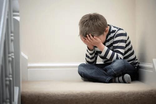 Junge sitzt traurig in der Ecke einer Treppe