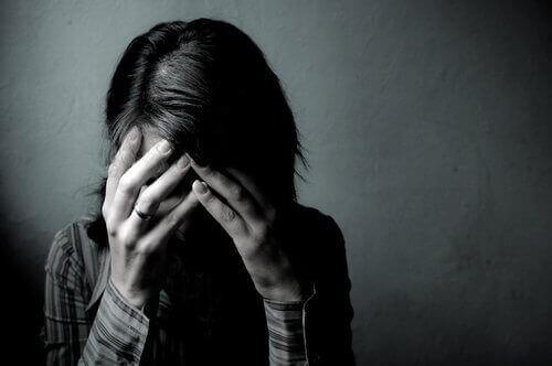 Eine Frau hat verzweifelt die Hände vor ihr Gesicht geschlagen.