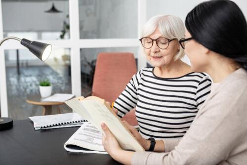 Eine ältere Frau im Gespräch mit einer jungen Psychologin in ihrem Büro.