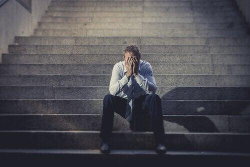 Ein Mann, der sich mit dem Gesicht in den Händen auf eine Steintreppe setzt.