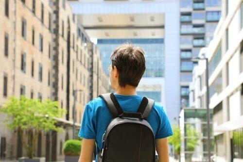 Ein Mann mit Rucksack und Blick auf eine Stadtstraße.
