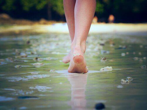 Ein Foto, das ein Paar Füße zeigt, die entlang eine Straße gehen, die in einer dünnen Schicht Wasser bedeckt wird.