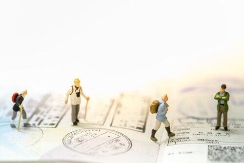 Kleine menschliche Figuren, die über einen Pass mit Rucksäcken und Spazierstöcken gehen.
