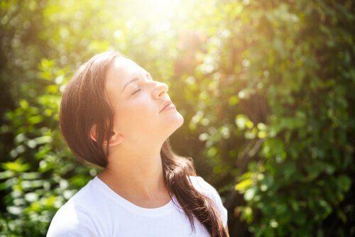 Ein Bild, das eine Frau zeigt, die oben mit ihren Augen schaut, schloss und die Natur um sie einließ.