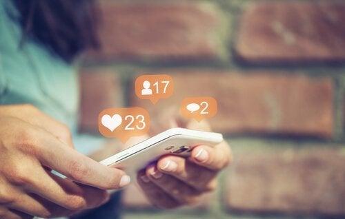 Eine Frau surft auf Instagram und nutzt dabei ihr Handy.