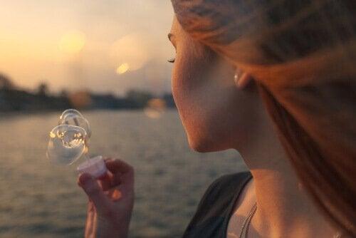 Frau macht Seifenblasen am See