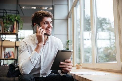 Ein Mann, der gleichzeitig sein Tablet und sein Handy benutzt.