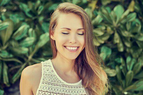Die Frau, die mit Augen lächelt, schließt während draußen.