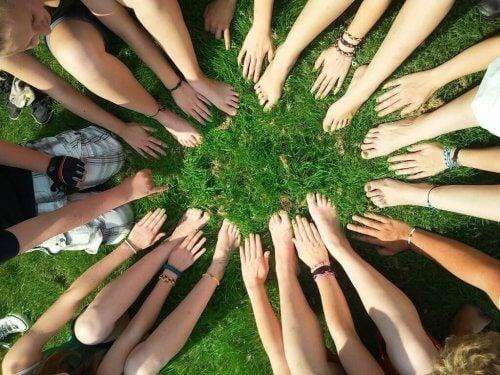 Menschen, die mit ihren kollektiven Händen und Füßen einen Kreis bilden.