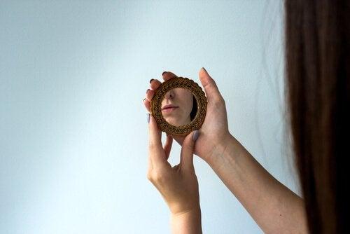 Eine Frau betrachtet ihr Spiegelbild in einem Handspiegel.