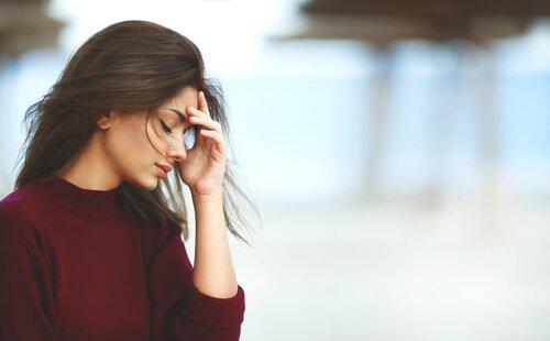 Eine Frau mit der Hand im Gesicht, die besorgt und frustriert nach unten schaut.