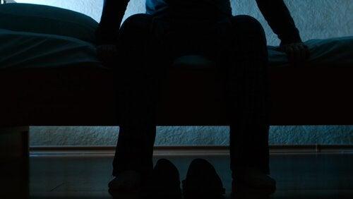 Mann, der auf dem Bett leidet unter unruhigem Beinsyndrom sitzt.