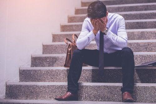 Mann sitzt verzweifelt auf einer Treppe