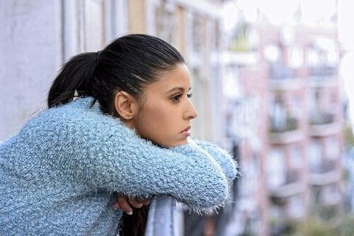 Eine Frau auf ihrem Balkon, in Gedanken versunken.
