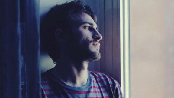 Trauriger Mann, der durch das Fenster schaut und versucht, sein inneres Selbst zu finden.
