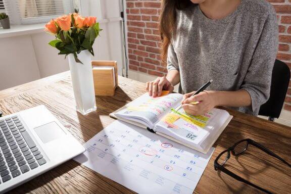 Eine Frau, die an einem Schreibtisch sitzt und Sachen in einem Lehrbuch hervorhebt.