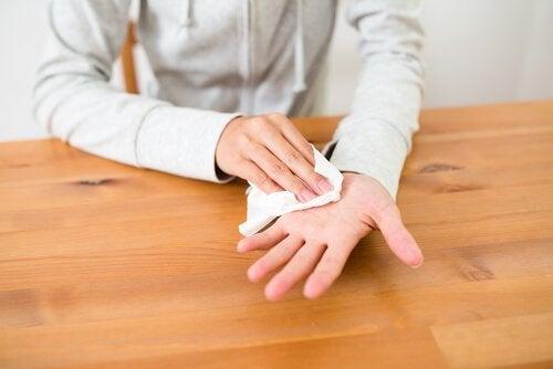 Eine Person, die ihre verschwitzte Hand mit einer Serviette abwischt.