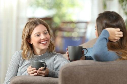 Freunde reden mit einer Tasse Kaffee in der Hand.