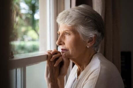 Eine ältere Frau schaut aus einem Fenster und braucht nicht-pharmakologische Therapie