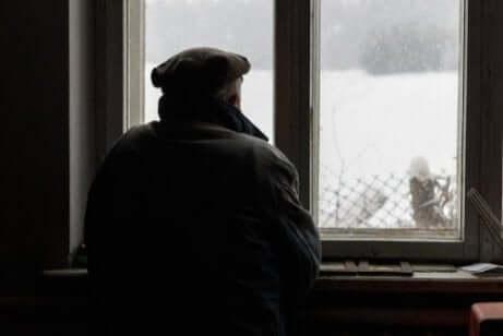 Ein alter Mann mit Alzheimer schaut aus dem Fenster.
