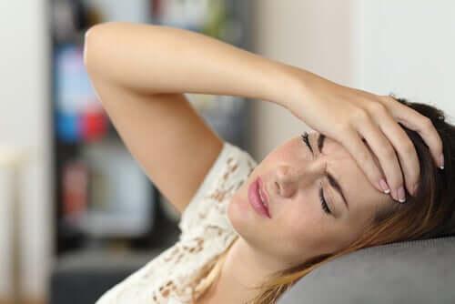 Frau mit Kopfschmerzen auf dem Sofa