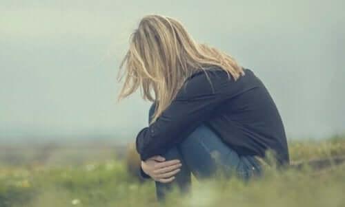 Eine Frau auf einem Feld, sich hinsetzend.