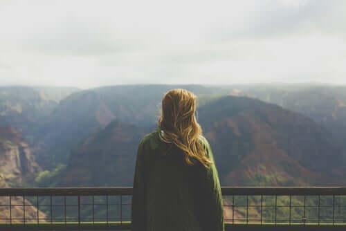 Frau vor Berglandschaft genießt ihre Freiheit