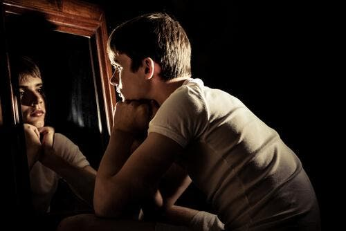 EinEin Junge mit niedrigem Selbstwertgefühl betrachtet sich im Spiegel.