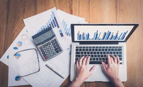 Hände auf Laptop neben Taschenrechner und Statistiken. Niemand ist unersetzbar!