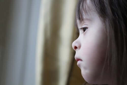 Ein Mädchen mit Down-Syndrom schaut aus dem Fenster.