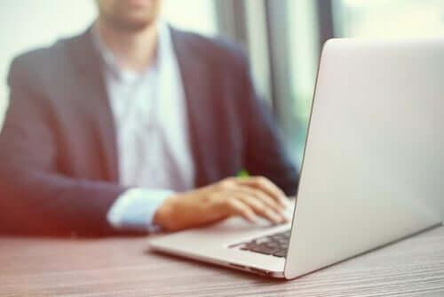 Mann liest Notizen auf einem Laptop