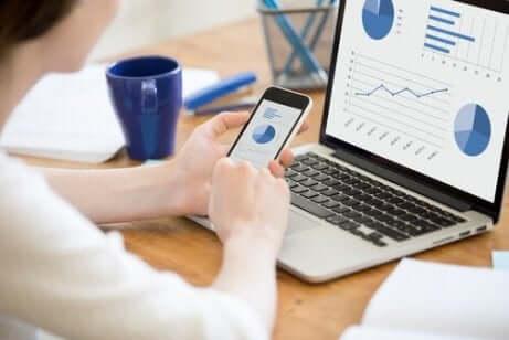 Eine Person, die ihr Telefon und Computer betrachtet. Statistische Begriffe auswerten.