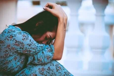 Eine traurige Frau, die sich mit ihren Armen auf ihrem Kopf hinsetzt.