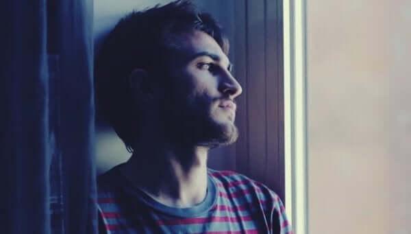 Trauriger Mann, der aus dem Fenster blickt - depressive Störung
