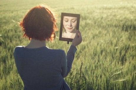Eine Frau, die auf einem Feld steht und sich selbst im Spiegel betrachtet, während sie darüber nachdenkt, den Weg zur Selbsterkenntnis einzuschlagen.