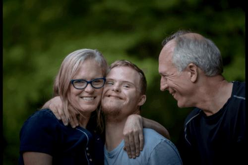 Zwei ältere Erwachsene und ein junger Mann mit Down-Syndrom. Bei gesitigen Behinderungen ist die Familie grundlegend.