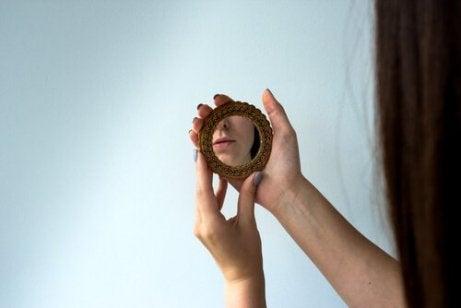 Ein Bild, das jemand zeigt, das einen kleinen Handspiegel mit einer Reflexion einer Ecke ihres Gesichtes hält.