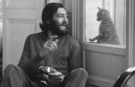 Cortázar sitzt am Fenster und spielt mit einer Katze auf der anderen Seite.