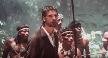 Ein Standbild aus dem Film, das Jeremy Irons mit einer Gruppe von Ureinwohnern hinter sich zeigt.