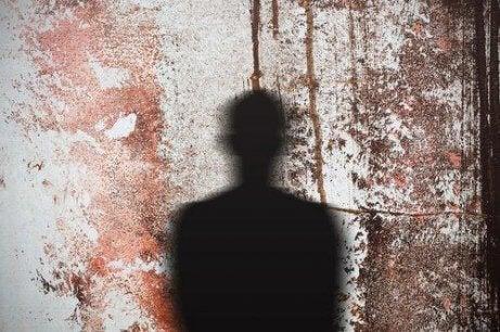 Der Umriss einer Person, die als Schatten auf eine Wand mit getrocknetem Blut geworfen wird.