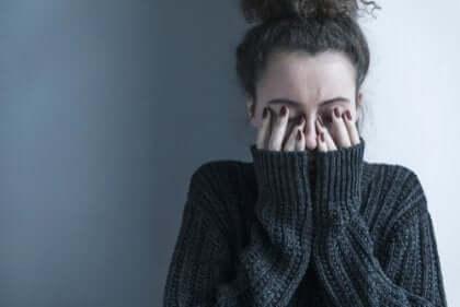 Eine Frau, die ihre Augen mit ihren Händen bedeckt.
