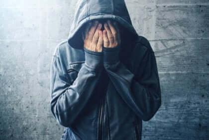 Ein Mann, der einen Hoodie mit den Händen über Gesicht trägt.