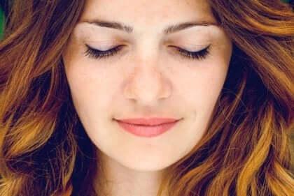 Eine Frau lächelnd mit geschlossenen Augen.