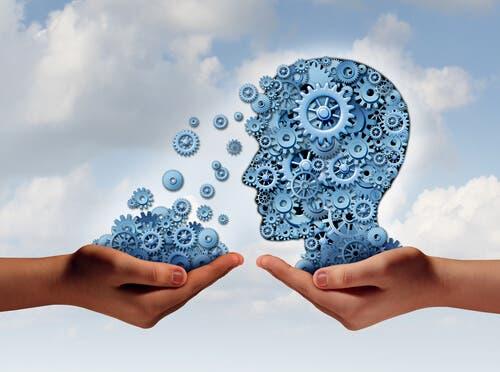 Zwei Hände halten Zahnräder - davon eine Hand Zahnräder in Form eines Kopfes. Gedankenkontrolle
