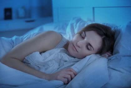 Eine Frau, die im Bett schläft und Ruhe und Erholung genießt.