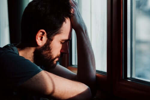 Trauma - Mann mit gesenktem Kopf am Fenster